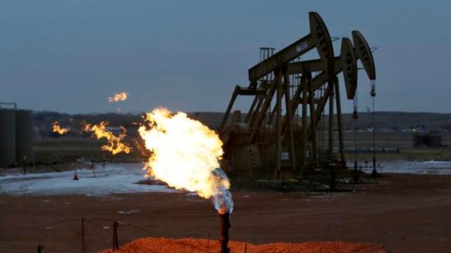 Dec. 17, 2014. Oil pumps work behind a natural gas flare near Watford City, N.D. (AP Photo/Eric Gay, File)